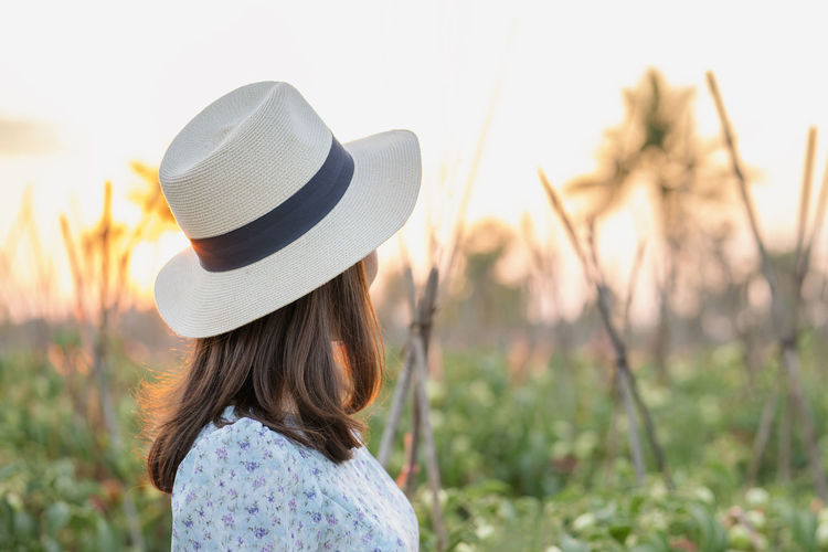 Rear view of woman with hat standing against plants