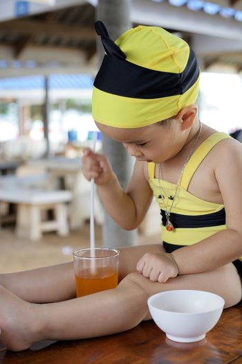 Cute Girl Looking At Juice While Sitting In Restaurant