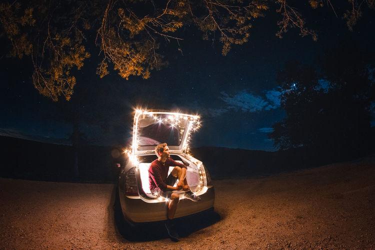 Man sitting in illuminated car at night