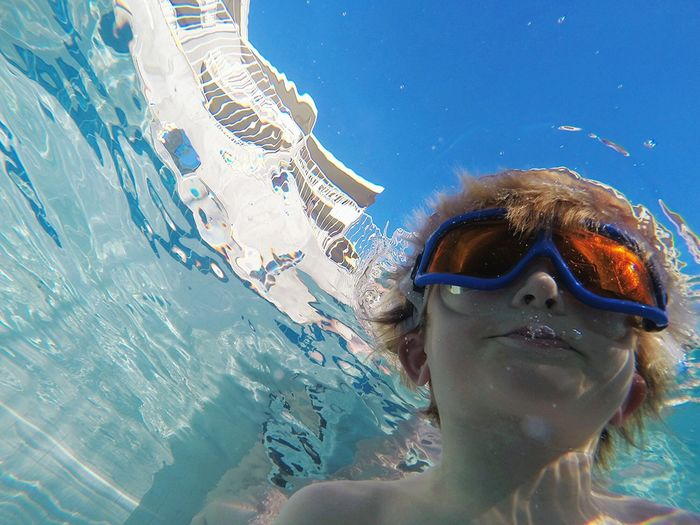 High angle view of shirtless boy swimming in pool against clear blue sky