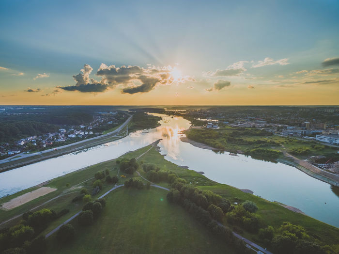 Scenic view of river against sky during sunset in city
