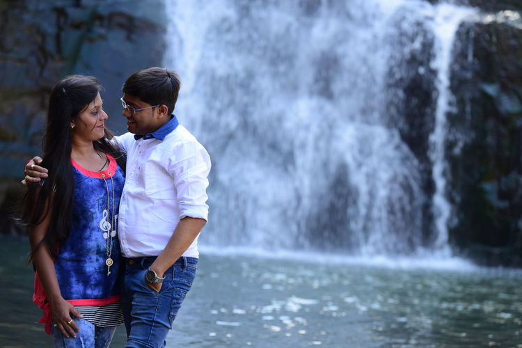 Young Couple Standing Against Waterfall