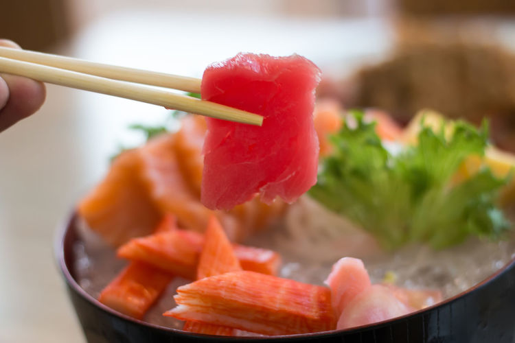 Cropped hand having sashimi served on table