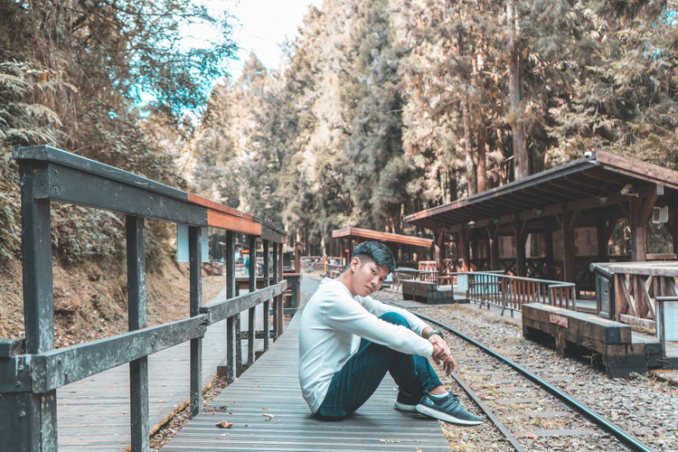 One Person Tree Sitting Real People Plant Architecture Full Length Lifestyles Built Structure Day Casual Clothing Nature Leisure Activity Men Rail Transportation Adult Track Railroad Track Males  Footbridge Outdoors Mature Men Teenager