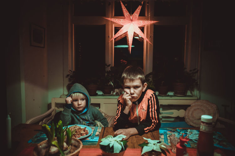 Christmas Boys Childhood Eating Food Food And Drink Front View Girls Indoors  Lifestyles Night Real People Sitting Star Table Togetherness Two People