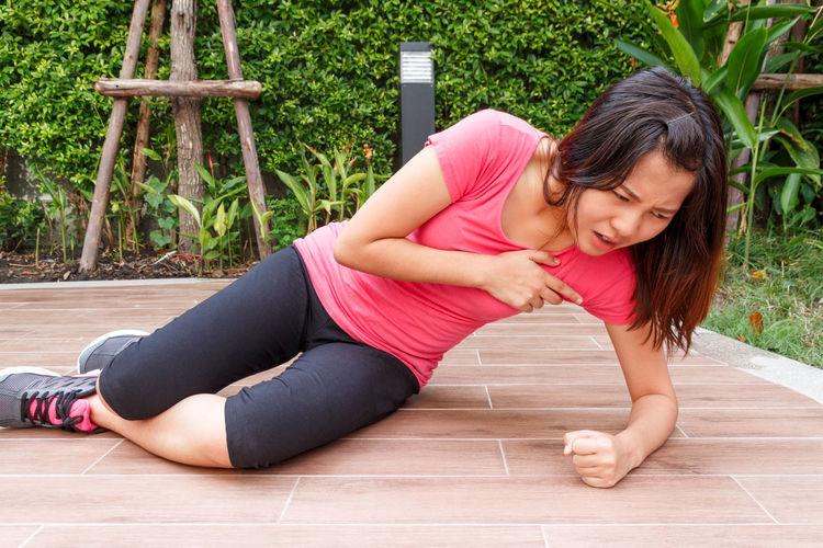 Woman suffering chest pain on hardwood floor in park