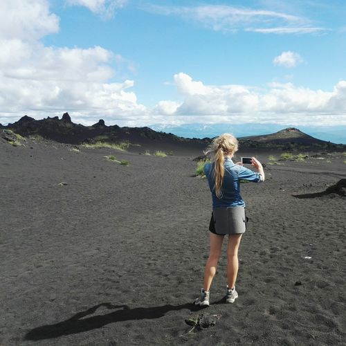 Rear View Of Woman Photographing Volcanic Landscape