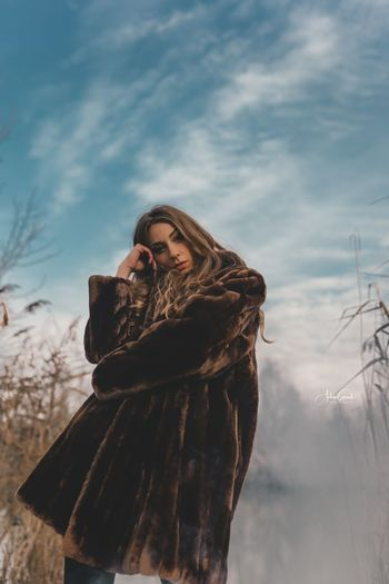 Woman looking at camera against sky