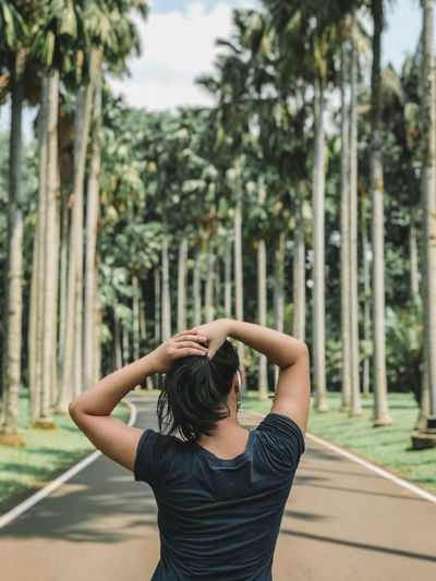 Rear view of woman standing against trees at park