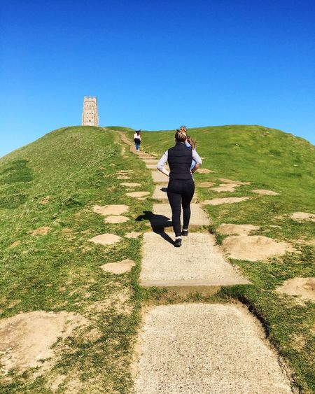 Glastonbury Tor Full Length Clear Sky Grass Rear View Shadow Sunlight Blue Walking Green Color Tranquil Scene Day Tourist Travel Destinations Tourism Footpath Outdoors Tranquility Solitude Getting Away From It All Vacations
