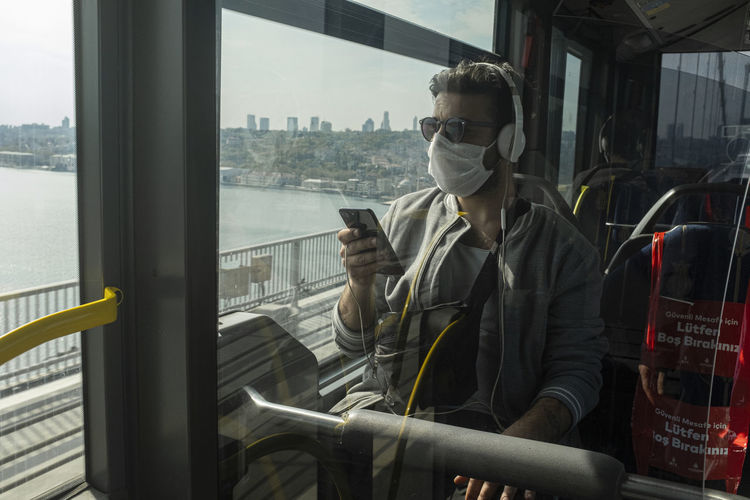 Man wearing mask while traveling in train
