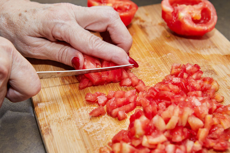 Cropped image of hand holding red chili peppers on cutting board