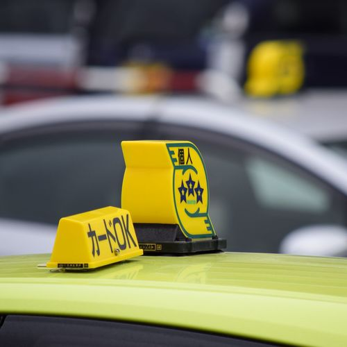 Close-up of yellow sign on car