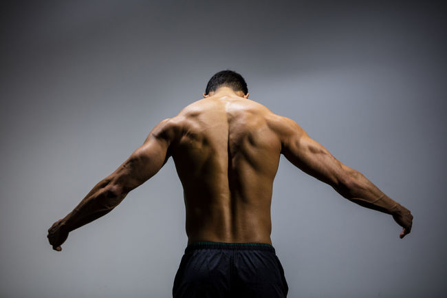A male fitness model displaying his chiseled physique. Adult Arms Asian  Human Body Man Rear View Shirtless Vietnamese Back Muscles Back Turned Chiseled Fitness Fitness Model Fitness Training Male Medium Shot Model Muscles Muscular Build Physique  Powerful Shoulders Strong Traps Triceps