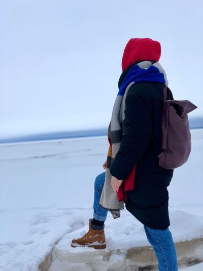 Side view of woman on snow covered land