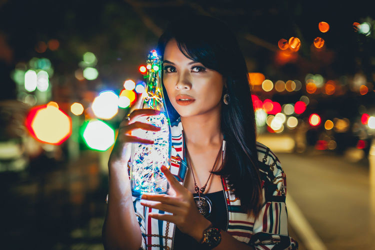 Portrait of young woman holding illuminated bottle while standing outdoors at night