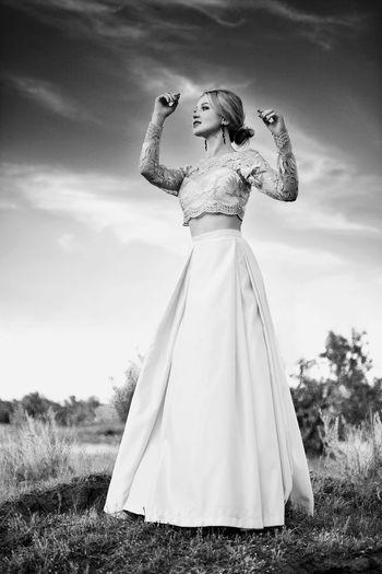 Full length of female fashion model standing against sky