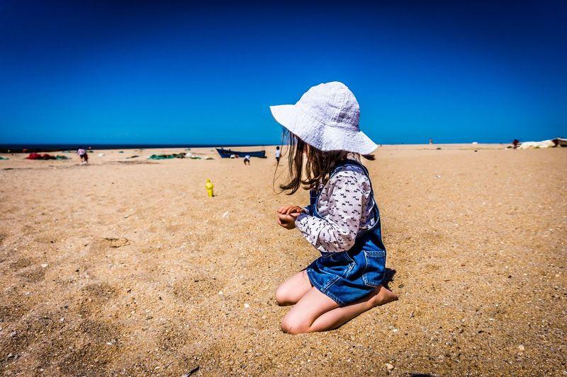 Full length of woman on beach against clear blue sky
