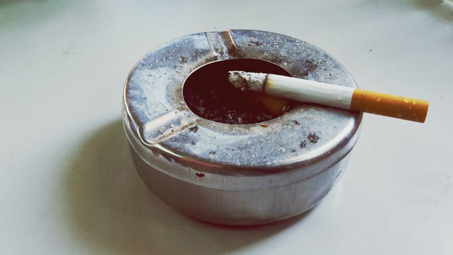 Close-up of cigarette in metallic ash tray on floor