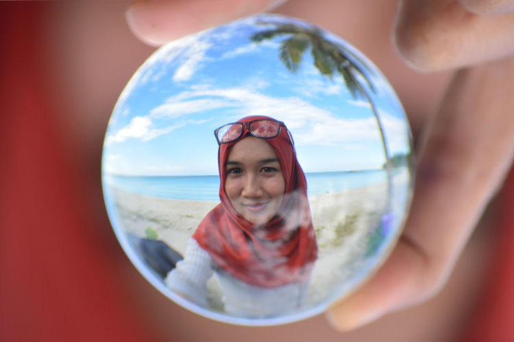 Cropped image of woman wearing red hijab reflecting on crystal ball at beach