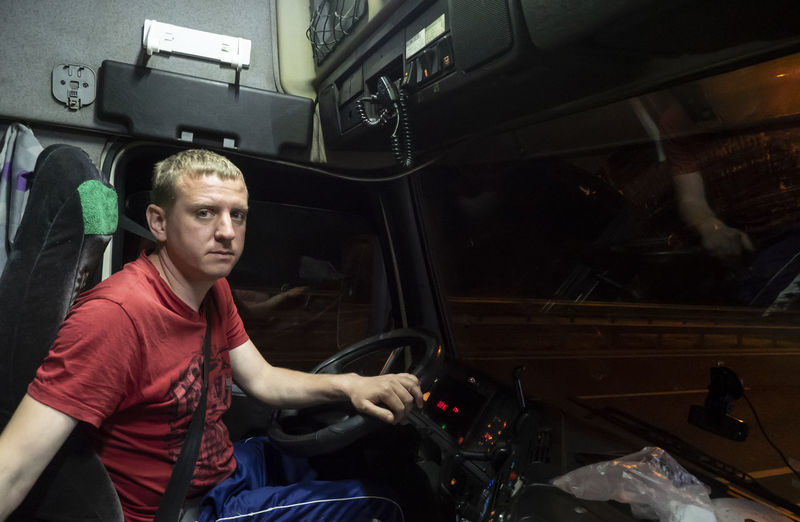 Portrait of man sitting in bus at night