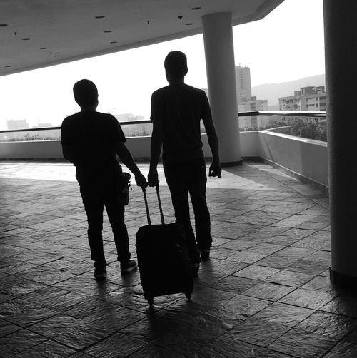 Silhouette of people standing with luggage