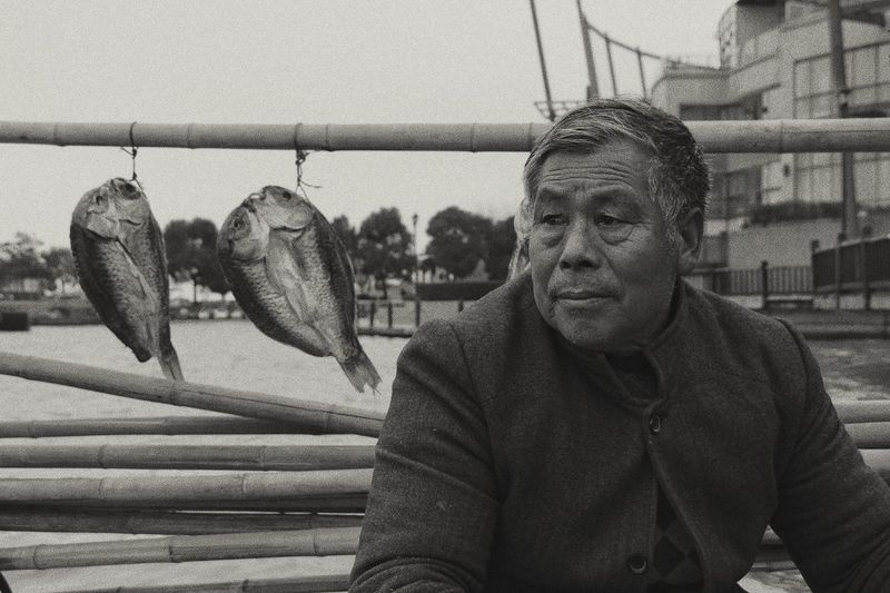 Portrait of man with fish hanging
