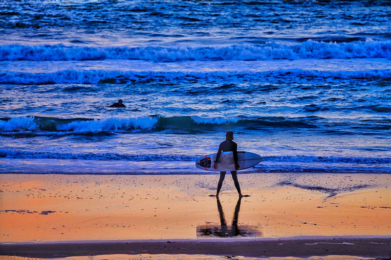 Rear view of man with surfboard standing at beach during sunset