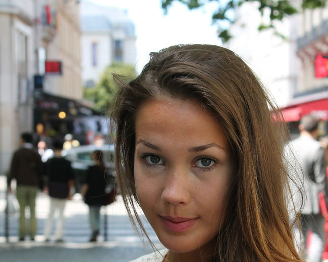 Close-Up Portrait Of Young Woman On Street In City