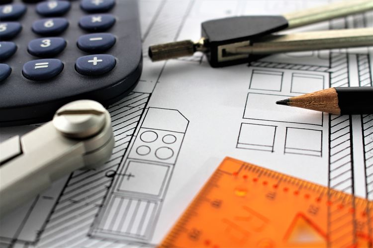 Close-Up Of Blueprint With Ruler And Calculator On Table