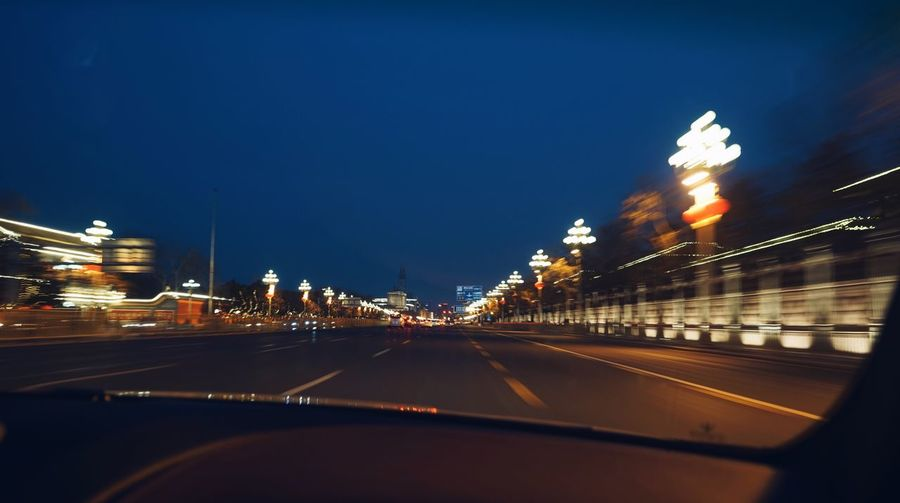 Light trails on road in city against clear sky at night