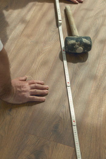 hand on freshly installed laminate floor next to rubber hammer and ruler Hand Close-up Installing Hardwood Floor Laminate Rubber Hammer Rubber Hammer High Angle View Working Measure Wood - Material Ruler Male Shadows Curtains Wood Indoors  Occupation Working Handyman Flooring Close Up Interior Renovation Home Industrial