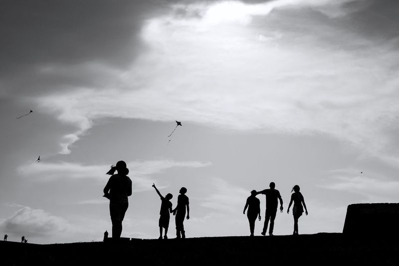 Black And White Photography Kite Monochrome Black And White Group Of People Cloud - Sky Sky Real People Leisure Activity Lifestyles Silhouette Medium Group Of People People Low Angle View Togetherness Outdoors