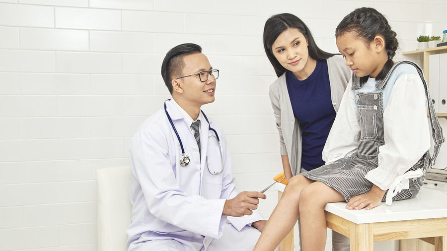 Doctor Examining Girl Sitting By Mother At Hospital