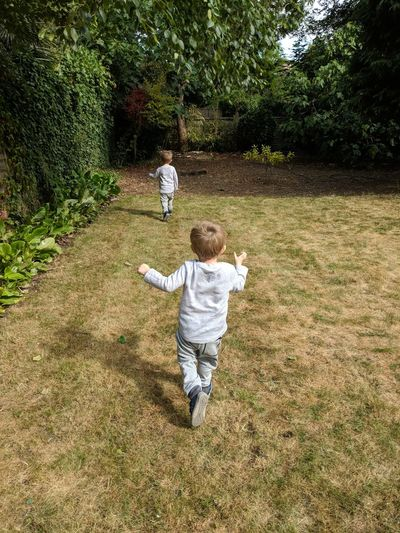 Rear view of twin boys running on grass against trees