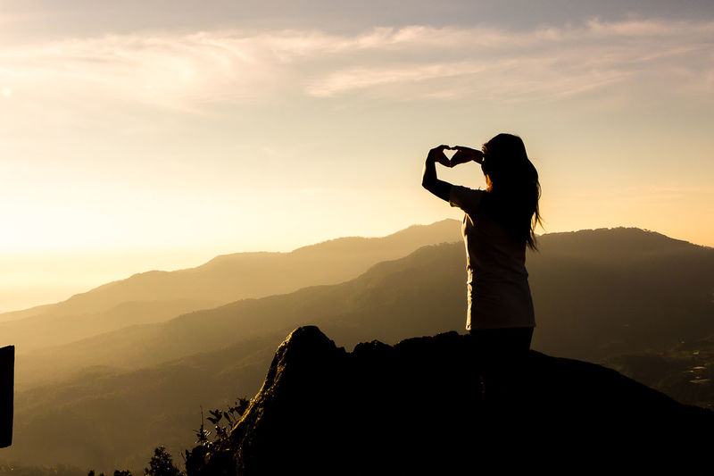 Silhouette woman on mountain against sky