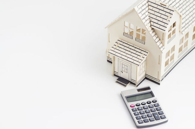 Real Estate Concept: House and calculator Construction Loan  Mortgage Broker Rate Agreement Architecture Asset Buy Calculator Copy Space Financing High Angle View Housing Investment New Development No People Real Estate Real Estate Agent White Background