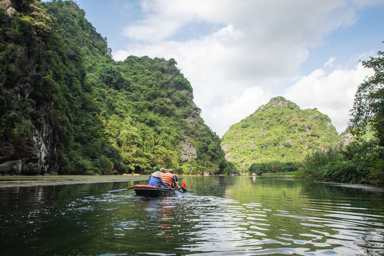tourist sitting on boat at Trang An, Ninh Binh, Vietnam. Water Tree Real People Beauty In Nature Plant Cloud - Sky River Nature Transportation Lifestyles Scenics - Nature Day Sky Nautical Vessel Mode Of Transportation Mountain Leisure Activity Non-urban Scene Men Outdoors