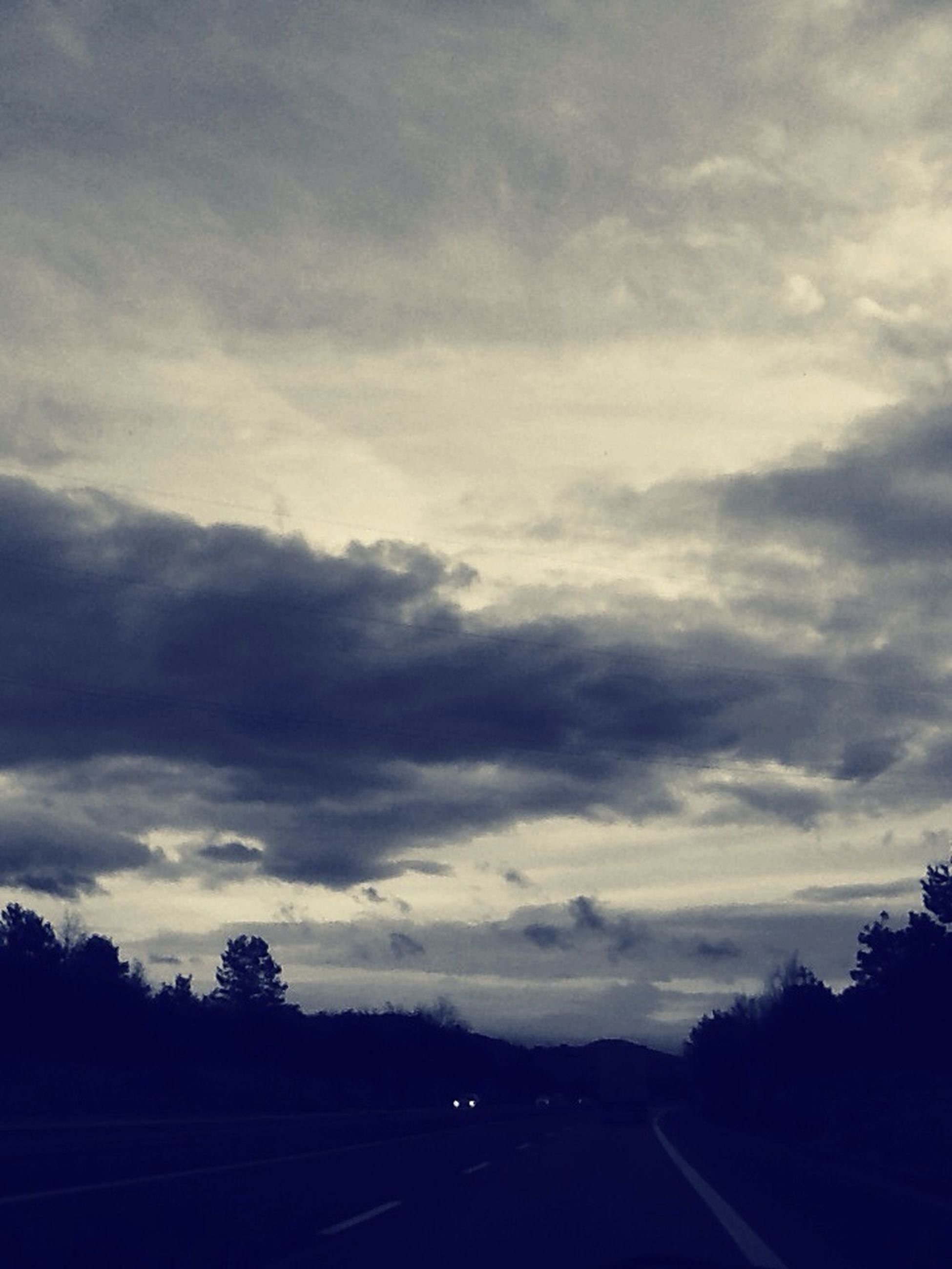 transportation, sky, road, cloud - sky, the way forward, silhouette, tree, cloudy, diminishing perspective, tranquility, tranquil scene, cloud, nature, scenics, landscape, beauty in nature, road marking, car, weather, vanishing point