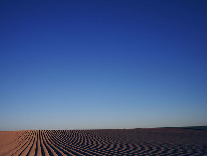 Scenic View Of Plowed Field Against Clear Blue Sky