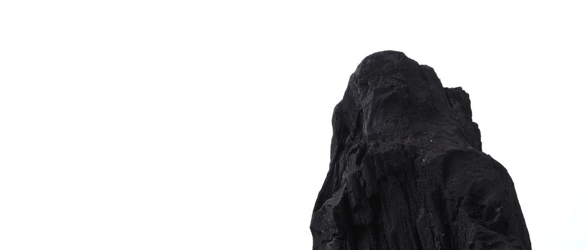 Low angle view of silhouette rock against clear sky