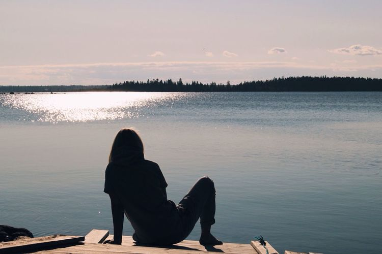 Silhouette Of Person Sitting By River