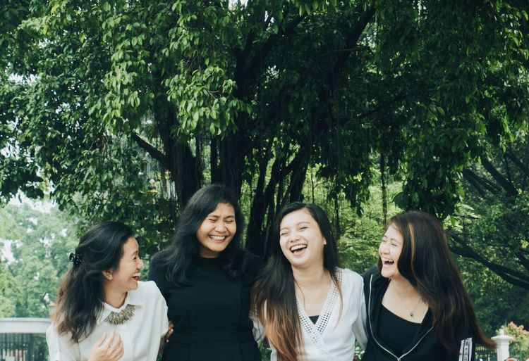 Cheerful female friends standing against trees