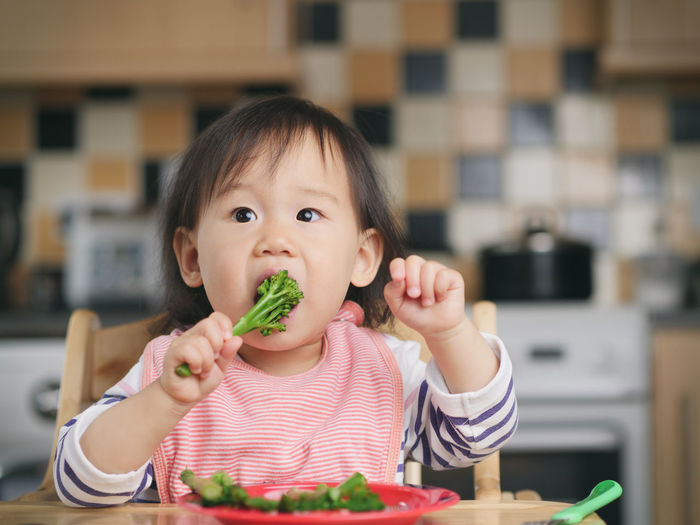 Baby girl eating vegetables while sitting on high chair at home