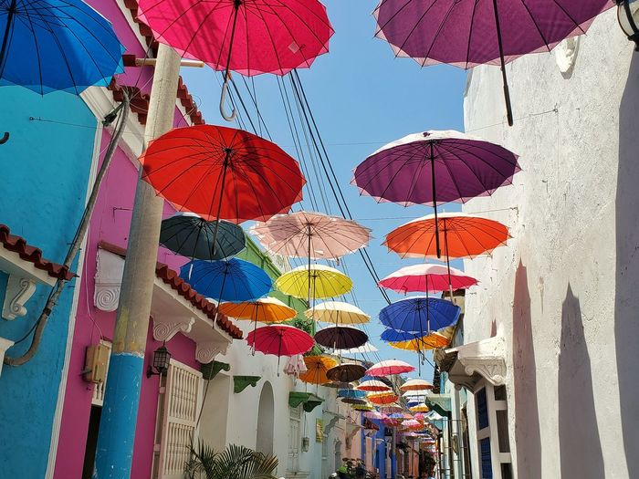 Low angle view of multi colored umbrellas hanging by building against sky