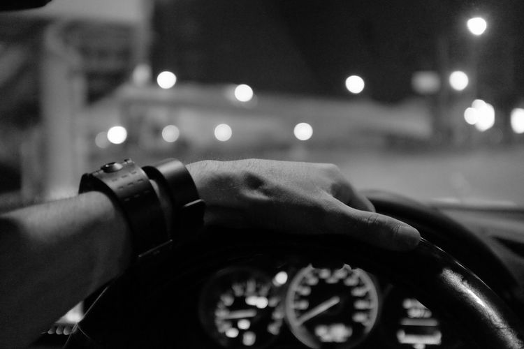 Cropped image of hand driving car at night