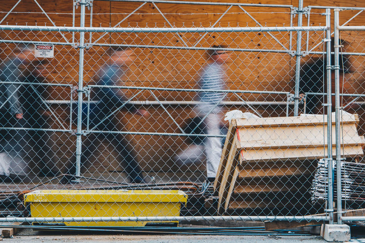 Blurred motion of people living busy lives in a city rushing around. - IG: @LostBoyMemoirs Streetwise Photography Streetphotography Street Photography People People Watching people and places Construction Site Chainlink Fence Mode Of Transportation Protection Boundary Blurred Motion Movement The Art Of Street Photography
