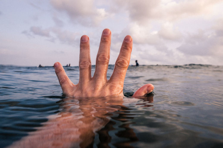 Person hand in sea against sky