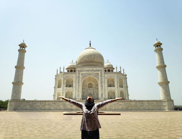 Woman with arms outstretched standing against taj mahal