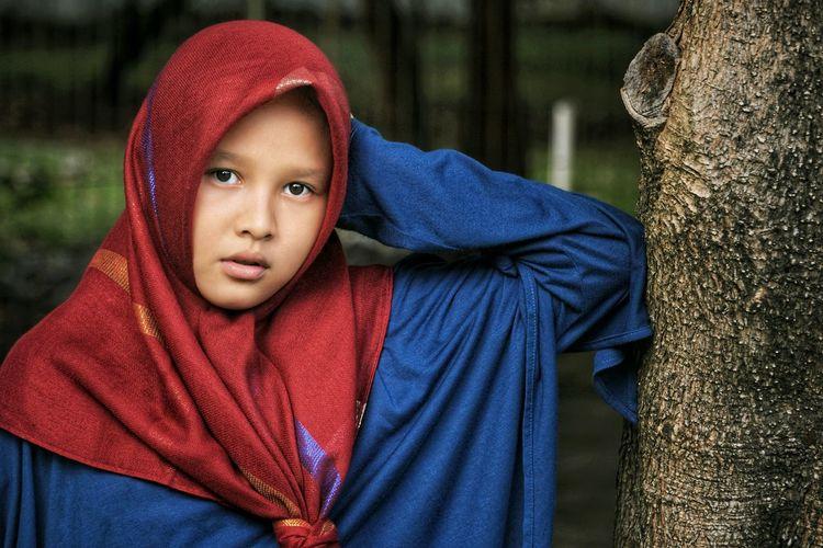 Portrait of girl by tree trunk